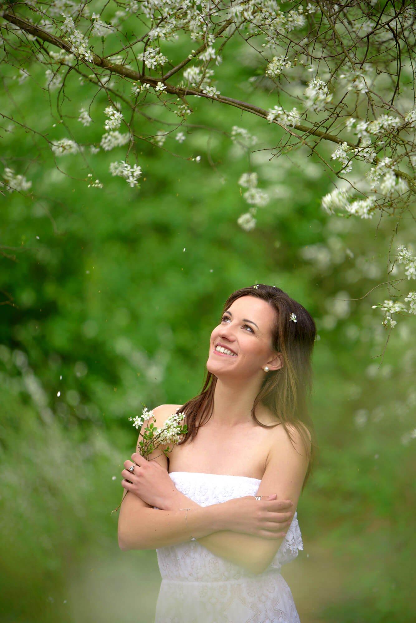 Aneta Štěpánková mezi kvetoucími stromy držící větvičky skvěty