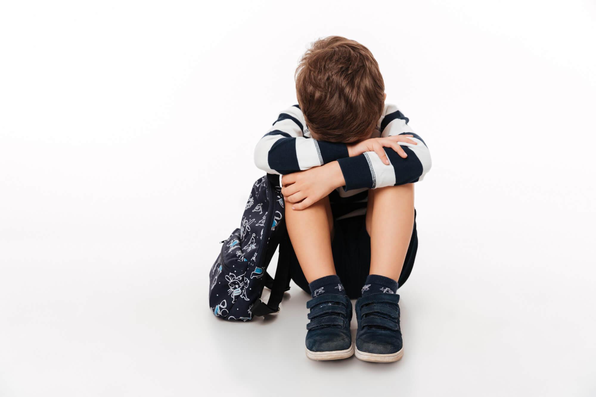 Chlapec sedí vedle batohu s hlavou v klíně
