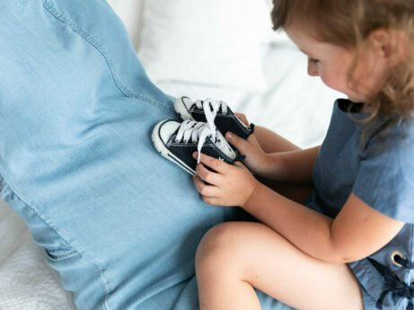 Holčička chodí s botičkami na břichu těhotné mamky