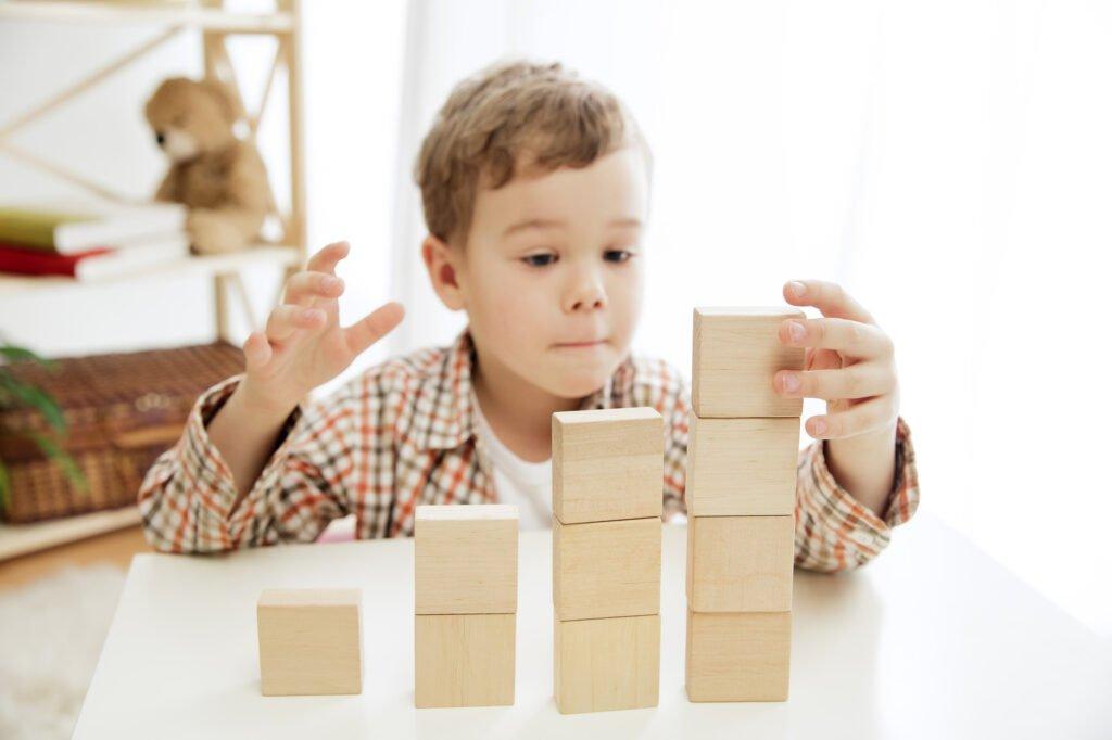 Chlapec staví dřevené kostky