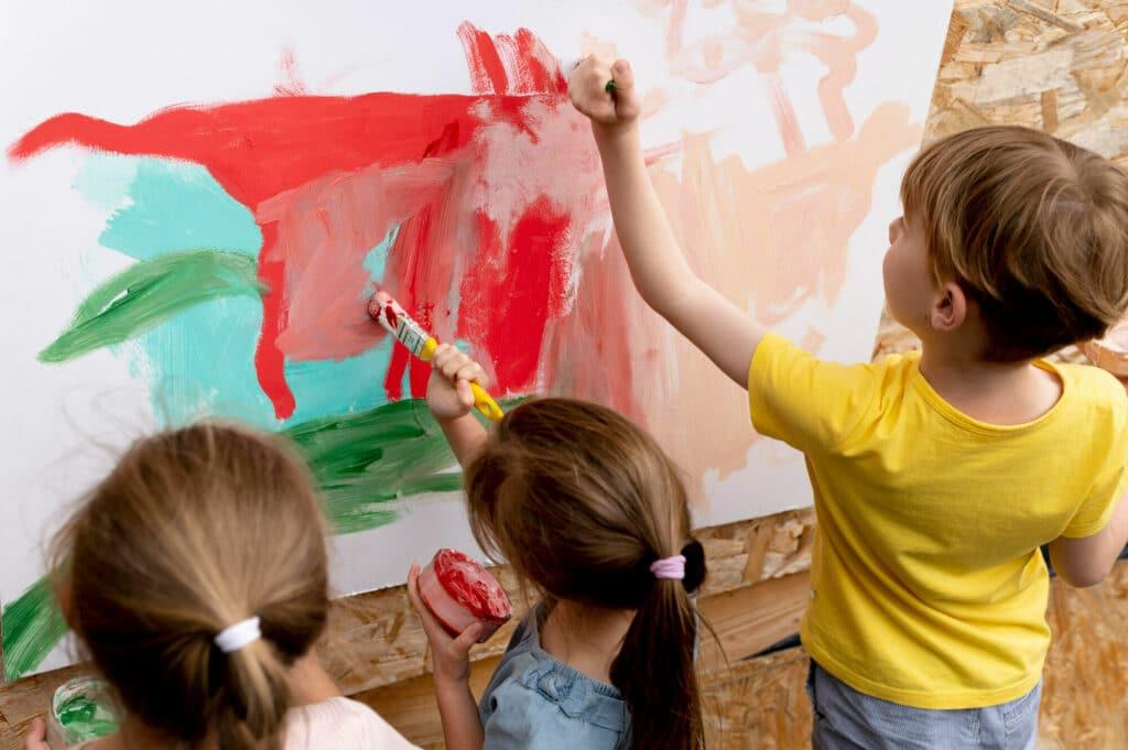 Děti společně malují temperami navelké plátno
