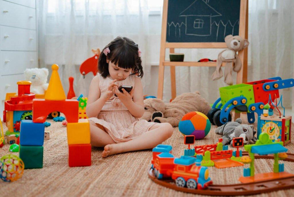 Holčička sedí mezi spoustou hraček